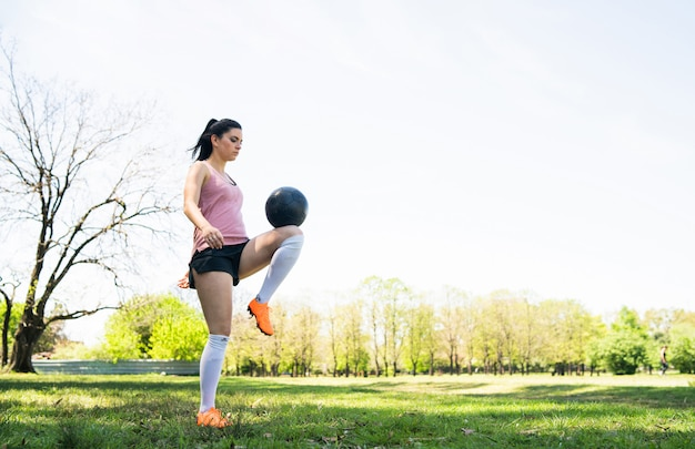 Portrait of young female soccer player training and practicing skills on football field. sports concept.