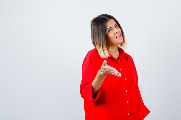 Ritratto di giovane donna che allunga la mano per salutare in camicia rossa oversize e guardare fiduciosa vista frontale