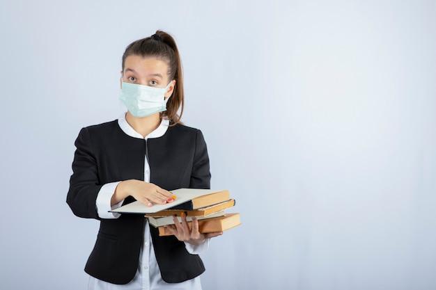 Ritratto di giovane studentessa leggendo un libro sul muro bianco. foto di alta qualità