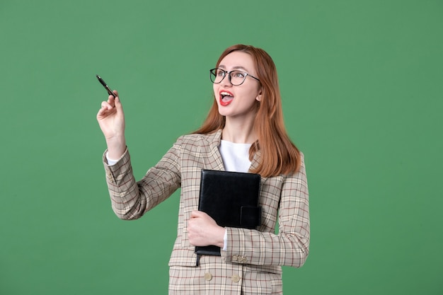 Portrait of young female teacher in suit with notepad on green