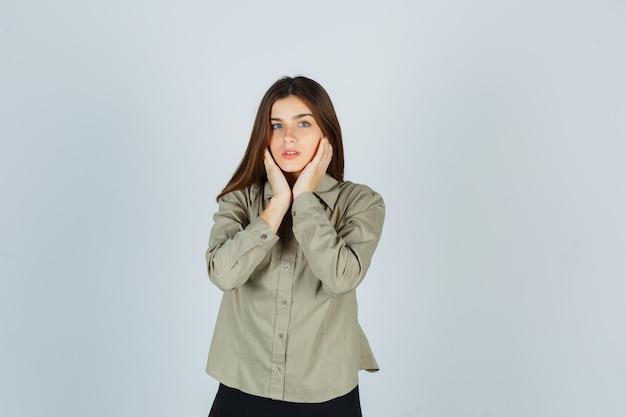 Ritratto di giovane donna che si tocca le guance con le mani in camicia, gonna e sembra una graziosa vista frontale
