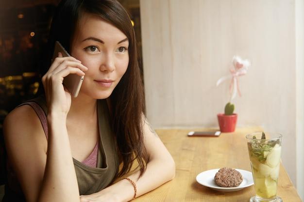 Ritratto di giovane donna con capelli castani utilizzando il telefono