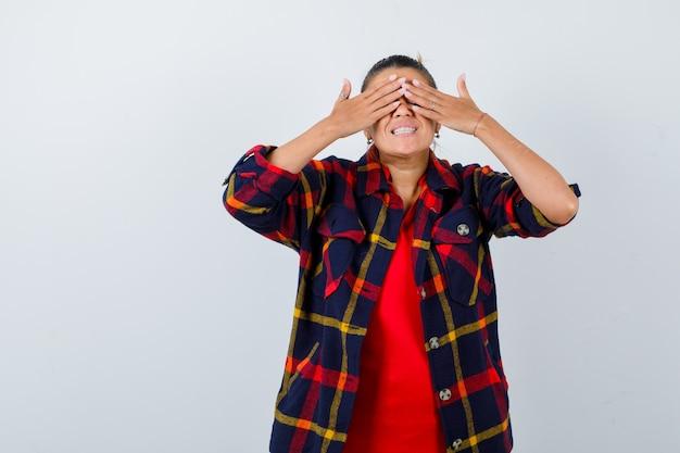 Ritratto di giovane donna con le mani sugli occhi in camicia a scacchi e guardando felice vista frontale