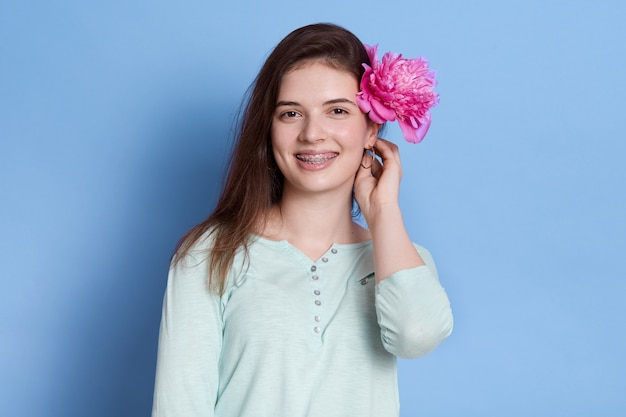 Portrait of young female with rose flower behind ear isolated over blue space