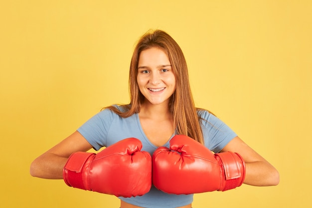 Portrait of young fighter woman wearing red boxing gloves on yellow background