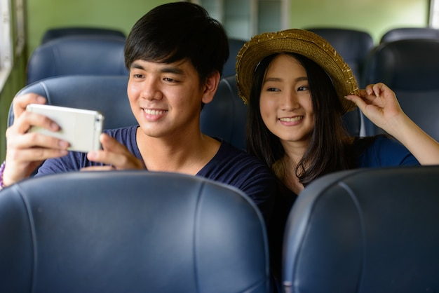 Portrait of young filipino tourist man and young asian tourist woman together and in love at hua lamphong railway station