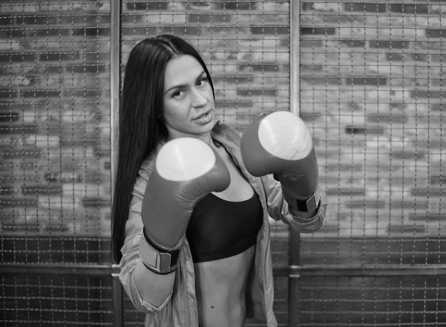 Portrait of young fit brunette in sporty underwear and pink coat posing in boxing gloves on the background of brick wall with steel mesh