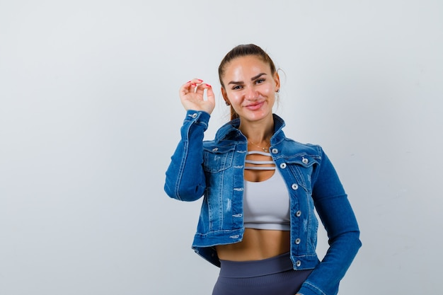 Portrait of young fit female showing claws imitating cat in top, denim jacket and looking joyful front view
