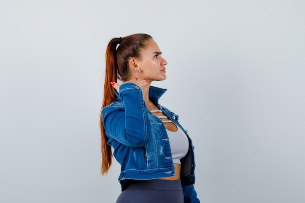 Portrait of young fit female touching skin on neck with fingers in top, denim jacket and looking aggressive