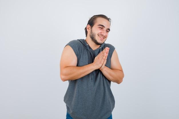 Ritratto di giovane maschio in forma tenendo le mani nel gesto di preghiera in felpa con cappuccio senza maniche e guardando grato vista frontale