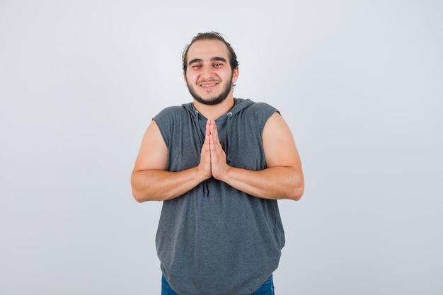 Ritratto di giovane maschio in forma che si tengono per mano nel gesto di preghiera in felpa con cappuccio senza maniche e in cerca di speranza vista frontale
