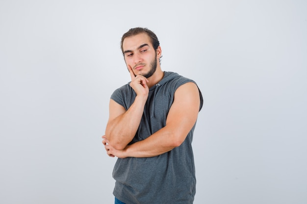 Portrait of young fit male keeping finger on cheek in sleeveless hoodie  and looking pensive front view