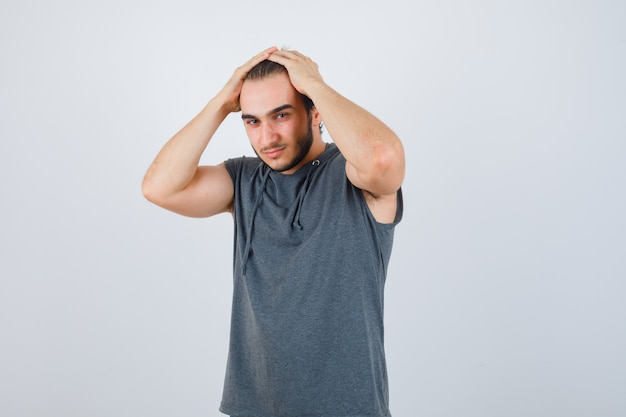 Portrait of young fit male keeping hands on head in sleeveless hoodie and looking attractive front view