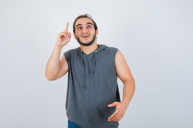 Portrait of young fit male pointing up while offering handshake as greeting in sleeveless hoodie  and looking cheerful front view