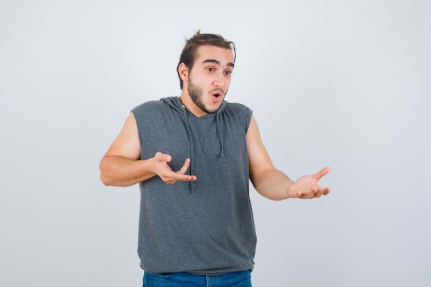 Portrait of young fit male showing something while pointing aside in sleeveless hoodie  and looking wondered front view