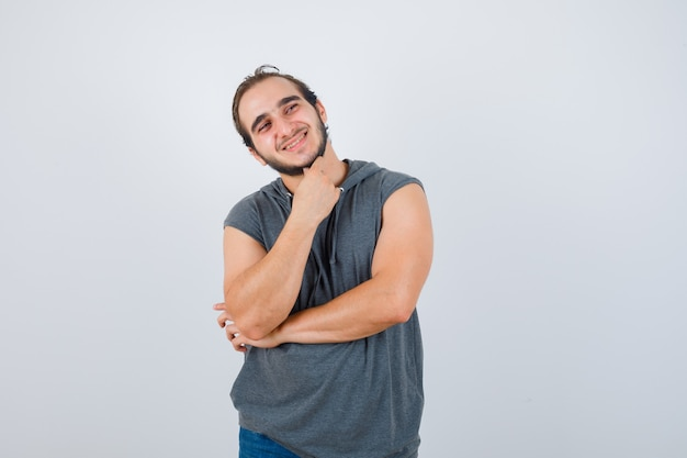Portrait of young fit male standing in thinking pose in sleeveless hoodie  and looking merry front view