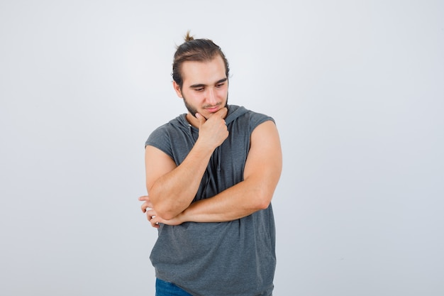 Portrait of young fit male standing in thinking pose in sleeveless hoodie  and looking pensive front view