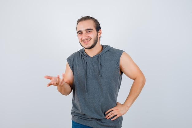 Portrait of young fit male streching hand towards camera in sleeveless hoodie  and looking joyful front view