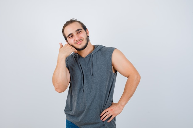 Portrait of young fit male touching cheek with hand in sleeveless hoodie  and looking merry front view
