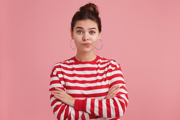 Ritratto di giovane donna lentiggini, infelice, sconvolta, in piedi con le braccia incrociate, accigliato e guardando, vestirsi in costume da bagno a strisce, isolato.