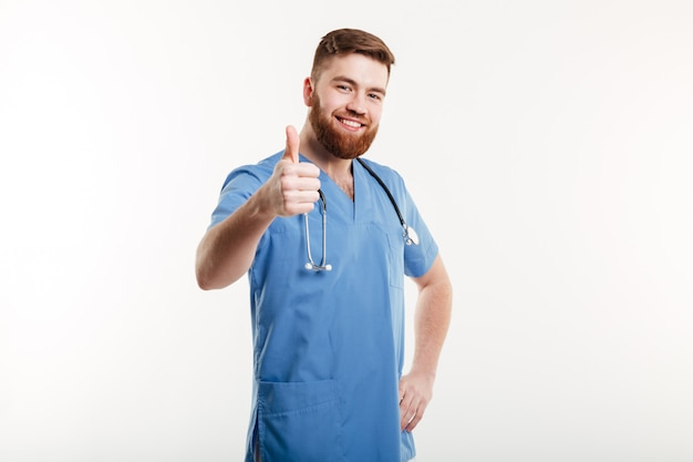 Portrait of a young friendly man doctor with stethoscope showing