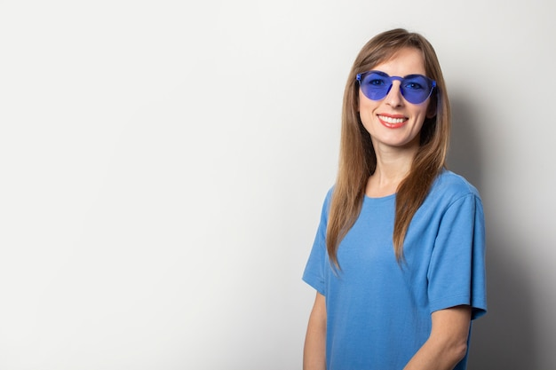 Portrait of a young friendly woman in casual blue t-shirt and blue glasses smiling on light. emotional face