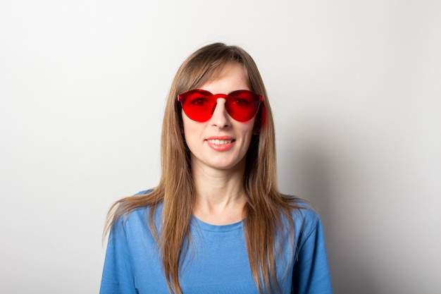 Portrait of a young friendly woman in casual blue t-shirt and red glasses smiling on isolated light. emotional face