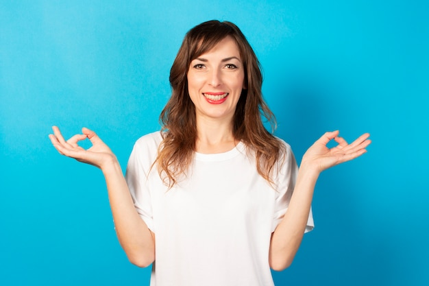 Portrait of a young friendly woman in casual t-shirt with gesture of meditation and smile on blue. emotional face. gesture to relax