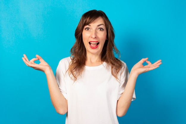 Portrait of a young friendly woman in casual t-shirt with a gesture of meditation and a surprised face on blue, relax