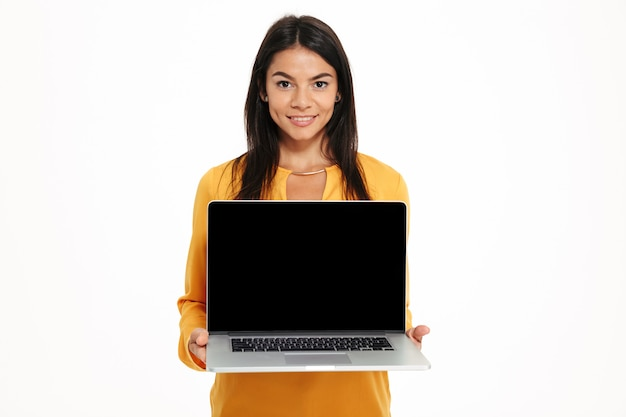 Portrait of young friendly woman showing blank screen laptop computer