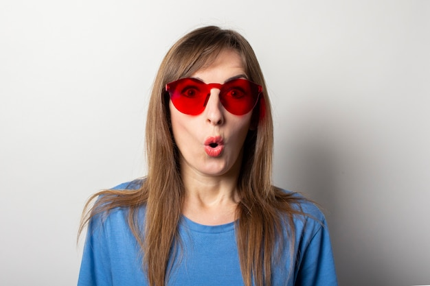 Portrait of a young friendly woman with a surprised face in a casual blue t-shirt and red glasses on light. emotional face