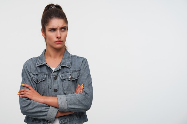 Portrait of young frown brunette lady wears in white t-shirt and denim jackets, looks away with disgusted expression, stands over white background with crossed arms.