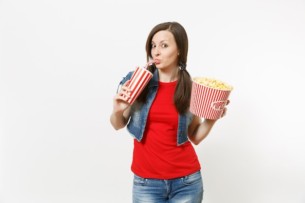 Portrait of young funny beautiful woman in casual clothes watching movie film, holding bucket of popcorn, drinking from plastic cup of soda or cola isolated on white background. emotions in cinema.