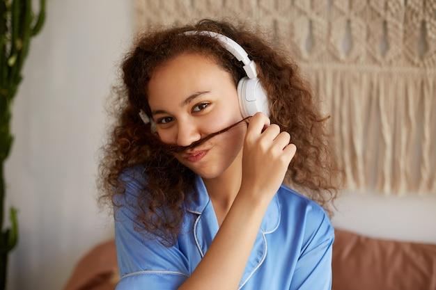Ritratto di giovane donna dalla pelle scura divertente con capelli ricci, fa i baffi da ciocche di capelli, ascolta la canzone preferita in cuffia e si sente bene.