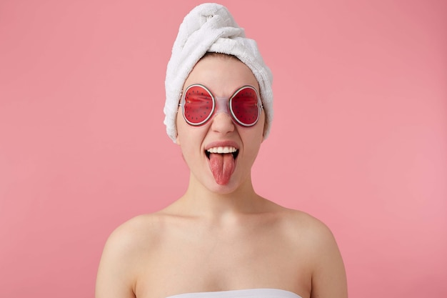 Portrait of young funny girl with mask on eyes, after shower with a towel on her head, shows tongue and stands.