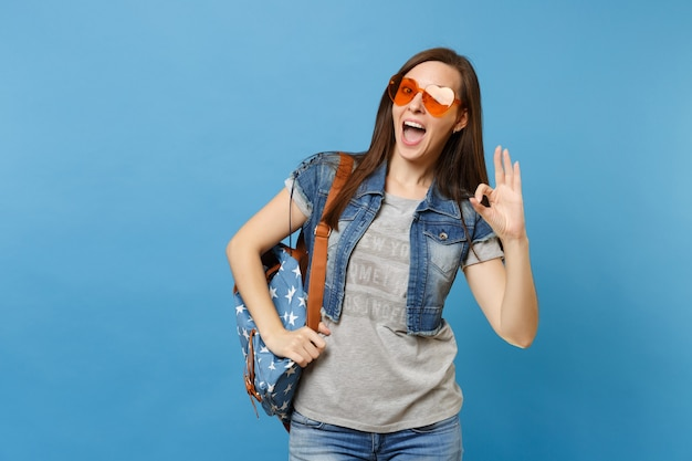 Portrait of young funny joyful woman student with backpack in denim clothes, orange heart glasses showing ok sign isolated on blue background. education in university. copy space for advertisement.