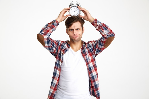 Portrait of a young funny man holding alarm clock