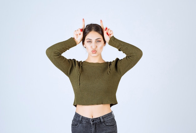 Ritratto di una giovane donna divertente modello in piedi e mostrando le orecchie da coniglio con le dita.