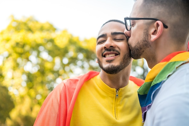 Portrait of young gay couple embracing and showing their love with rainbow flag in the stret. lgbt and love concept.