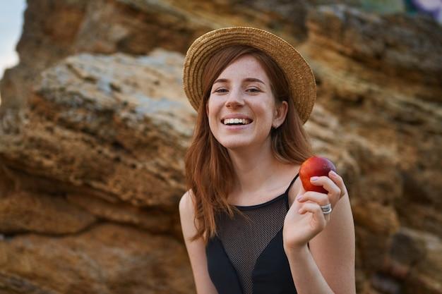 Ritratto di giovane signora bella lentiggini zenzero sulla spiaggia, indossa un cappello, mangia una pesca, in generale sorride e guarda la telecamera, sembra positivo e felice.
