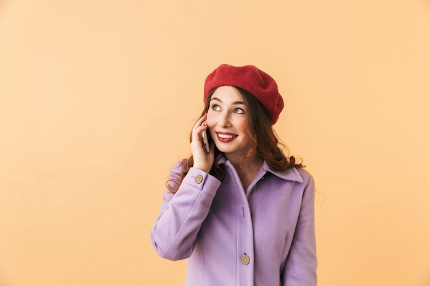 Portrait of young girl 20s in coat and hat using smartphone for call, while standing isolated