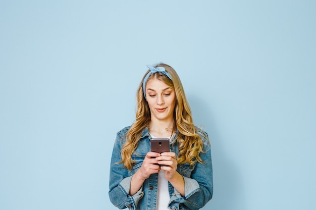 Portrait of a young girl amazed why she sees in her mobile phone isolated on a blue background