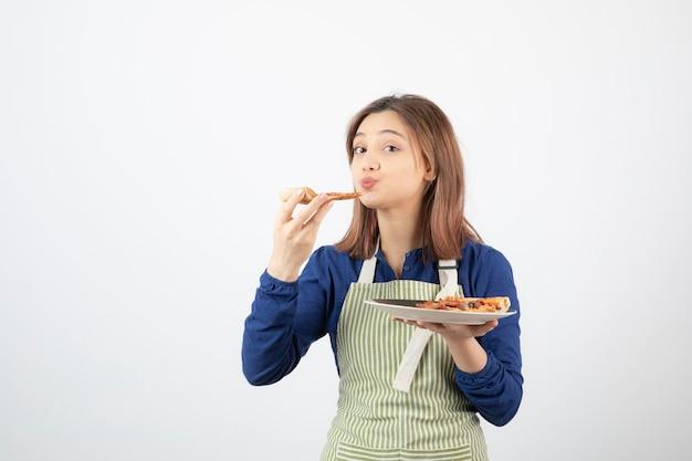 Ritratto di giovane ragazza in grembiule che mangia pizza su bianco