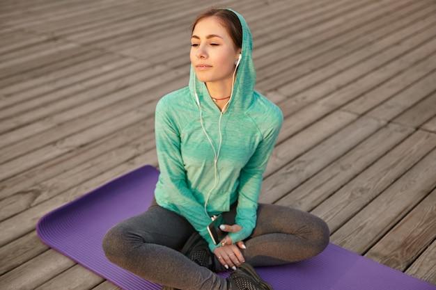 Ritratto di giovane ragazza in abiti sportivi luminosi, ascoltando la canzone preferita in cuffia dopo lo yoga mattutino e godersi il sole.
