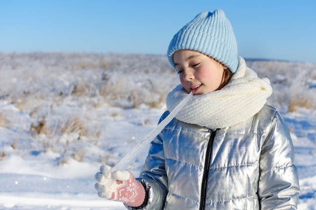 Portrait of young girl eating icicle on sunny winter day.