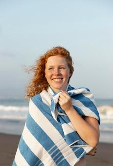 Ritratto di giovane ragazza che gode del tempo in spiaggia