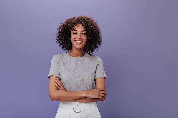 Ritratto di giovane ragazza in maglietta grigia sul muro viola