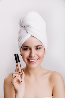 Portrait of young girl in great mood on white wall. woman with towel on her head posing with concealer.