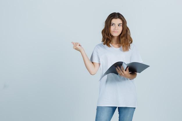 Ritratto di giovane ragazza che tiene la cartella, che punta indietro con il pollice in t-shirt bianca e guardando esitante vista frontale