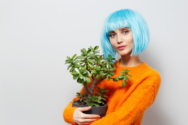 Portrait of young girl holding pot of flower against white background. wearing orange sweater.